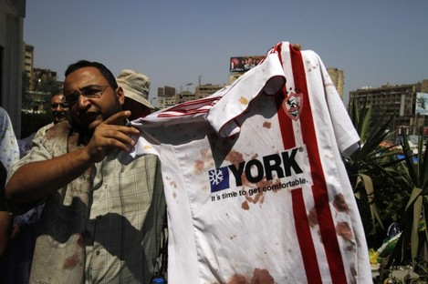 A man displays a bloodied shirt of ousted President Mohamed Morsi's supporter outside a local hospital in Cairo