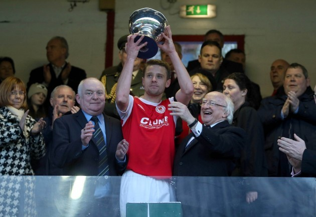Greg Bolger lifts the cup as Paddy McCaul and Michael D. Higgins look on