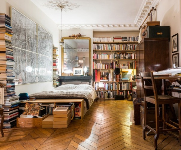 Bookshelves and stacks of books in this...