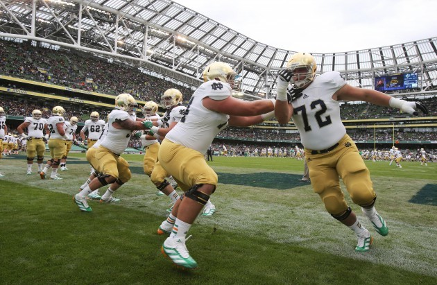 Notre Dame players do warm up drills