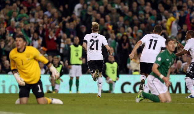 Marco Reus celebrates scoring the first goal as Keiren Westwood and Stephen Ward kneel in dejection
