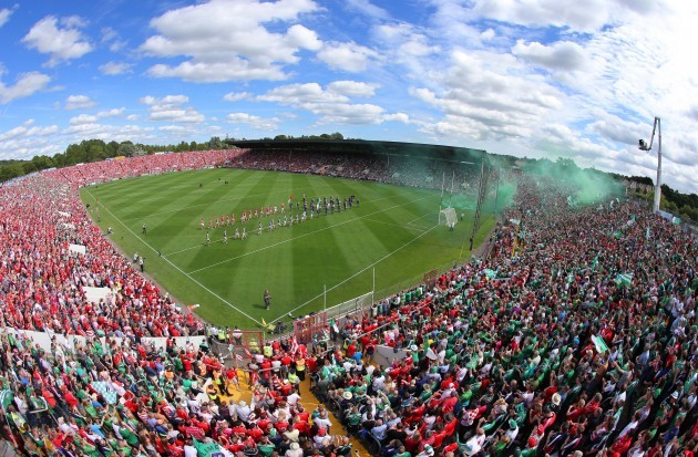 Cork and Limerick players walk behind the band