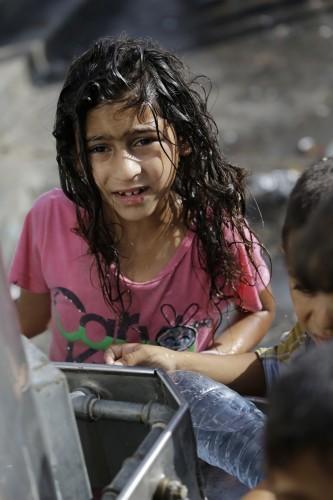 A displaced Palestinian child collects water, at the Abu Hussein U.N. school, in Jebaliya refugee camp, northern Gaza Strip