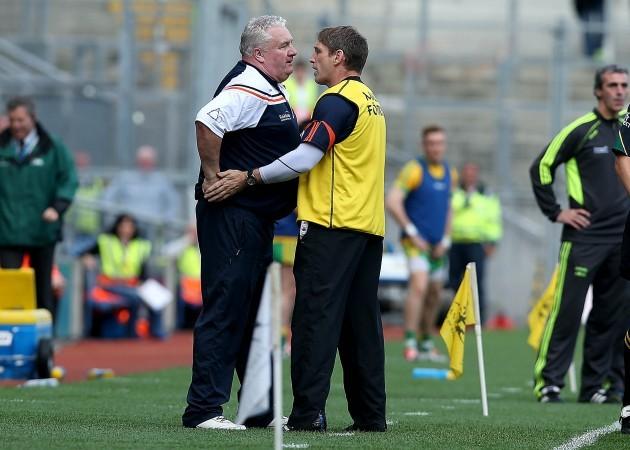 Paul Grimley is held back by Kieran McGeeney
