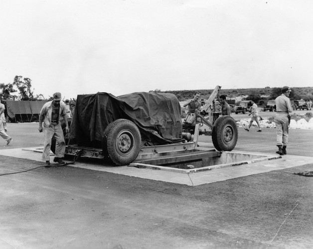 at-the-airfield-fat-man-is-lined-up-over-a-pit-specifically-constructed-for-it-from-which-it-is-then-loaded-into-the-plane-that-eventually-dropped-it-over-nagasaki