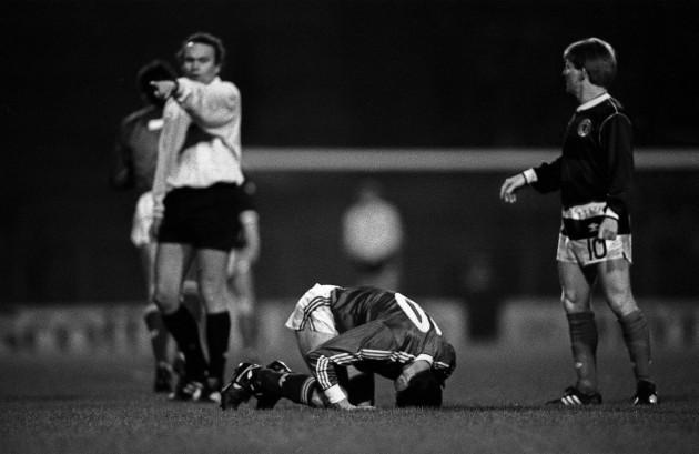 Gordon Strachan stands over an injured John Aldridge