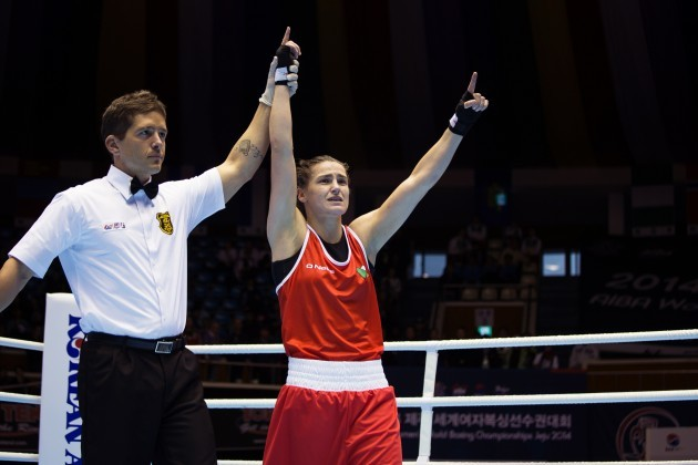Katie Taylor has her arm raised by the referee after the judges declared her the winner