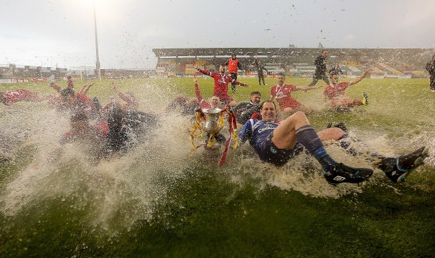 Sligo Rovers players celebrate on the rain soaked pitch at the end of the game