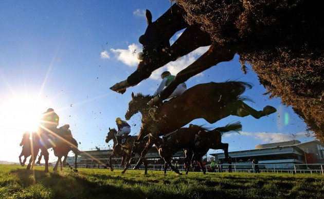 Riders and runners clear a hurdle