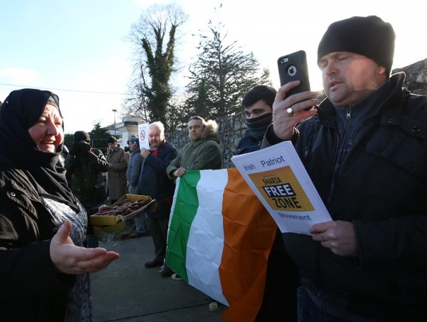 Protester tears up anti-Islam banner at Clonskeagh Mosque march