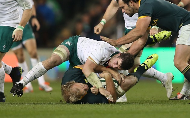 Schalk Burger is tackled by Peter O'Mahony