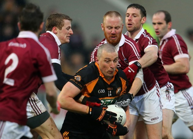 Kieran Donaghy is tackled by Brendan Rodgers, Conan Cassidy and Barry McGuigan