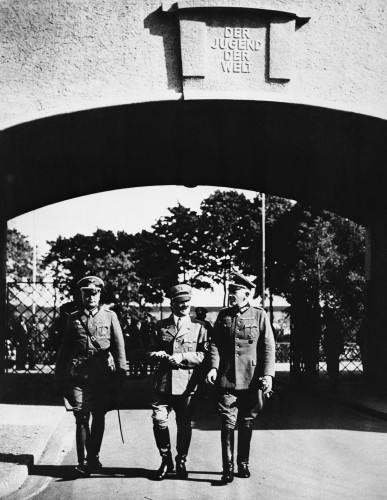 here-we-see-hitler-center-and-two-aides-enter-the-olympic-village-for-an-inspection-the-gateway-inscription-reads-to-the-youth-of-the-world