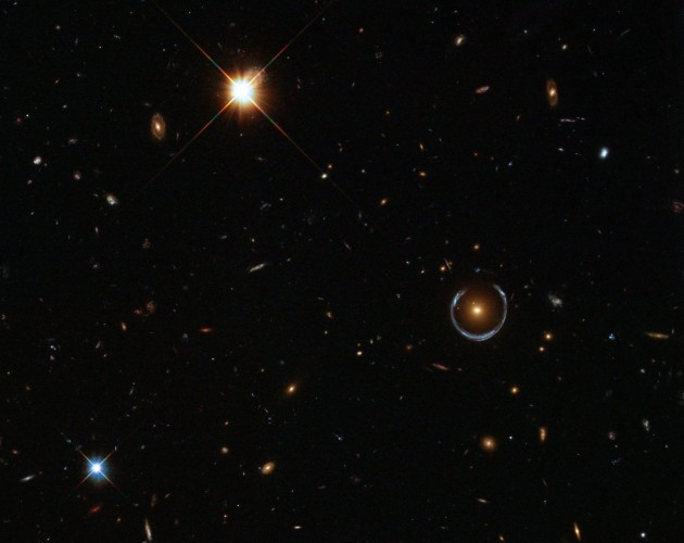 believe-it-or-not-this-is-a-real-hubble-image-and-that-bizarre-blue-ring-toward-the-right-is-an-optical-illusion-produced-when-gravity-bends-light-in-a-phenomenon-called-gravitational-lensing-astr