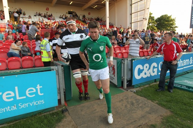Ronan O'Gara of Ireland and Mick O'Driscoll from Munster who captained the Barbarians lead their teams out