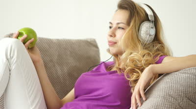 stock-footage-attractive-young-woman-relaxing-on-sofa-listening-to-music-on-headphones-and-holding-green-apple
