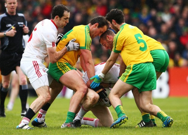 Hugh McFadden, Neil McGee and Ryan McHugh tackle Cathal McShane