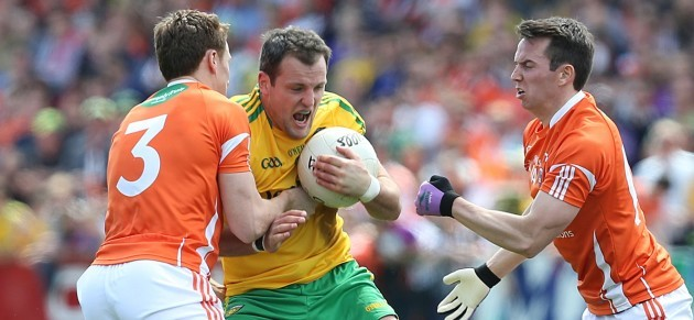 Michael Murphy is tackled by Charlie Vernon and Tony Kernan