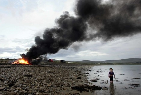 Feast of St John. Three-year-old Josephine McHale looks for her dog as a bonfire burns in the background celebrating the Feast of St John today outside of Belmullet, County Mayo. During the Feast many years ago a bull was slaughtered