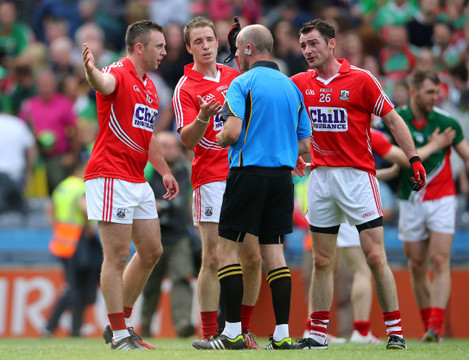 Cork players surround referee Cormac Reilly