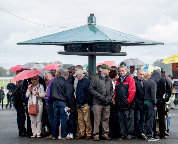 Punters shelter from a rain shower