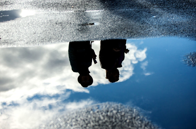 A view of punters reflected in a puddle