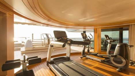 the-boat-includes-a-gym-with-state-of-the-art-equipment-that-has-a-stunning-view-out-onto-the-bow-of-the-vessel-a-giant-sliding-door-reveals-the-outside-and-can-let-a-breeze-in-the-area-leads-into-the-pool-if