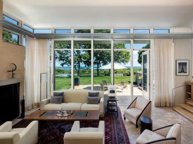 an-open-living-room-with-a-fireplace-and-floor-to-ceiling-windows-brings-the-outdoors-in