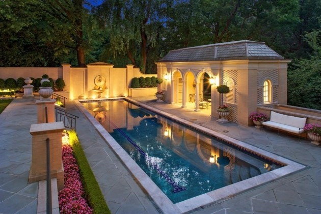 theres-an-indoor-pool-as-well-as-an-adjacent-poolhouse-among-an-immaculately-landscaped-backyard-surrounded-by-greenery