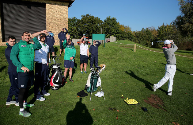 Rory McIlroy tees off as the Irish players watch on