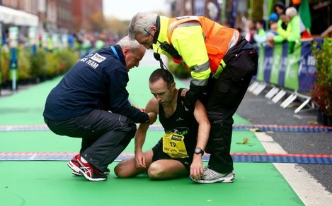 Gary O'Hanlon is assisted at the finish line