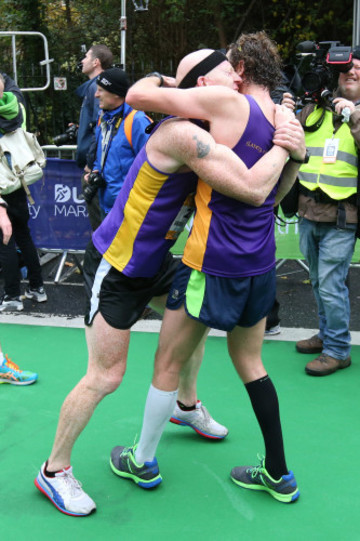 Competitors embrace after finishing the Dublin City Marathon