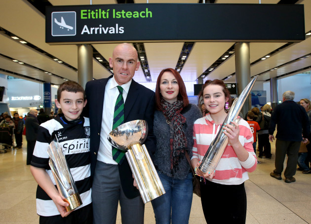 Trent Johnston arrives home bearing gifts, the three international trophies won with Ireland this year and is greeted by his family Charlie, Vanessa and Claudia Johnston