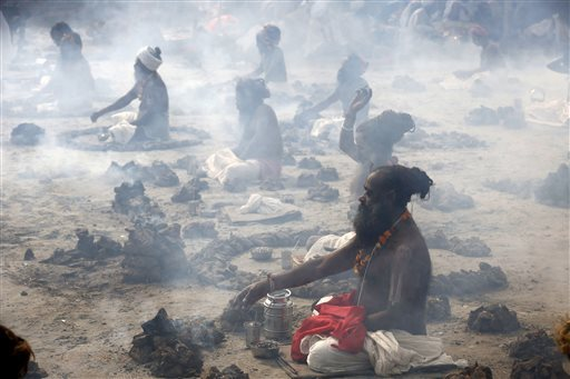 Hindu holy men performing a ritual by burning dried cow dung cakes in earthen pots at Sangam.