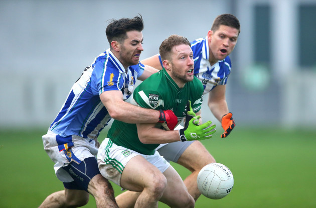 Cahir Healy is tackled by Michael Darragh Macauley and Conal Keaney