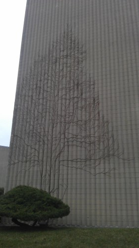 The ivy growth on the side of this building looks like a tree.