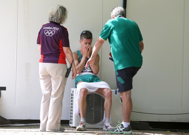 A dejected Rob Heffernan is consoled by an Olympic volunteer and Patsy McGonagle after finishing 4th 11/8/2012