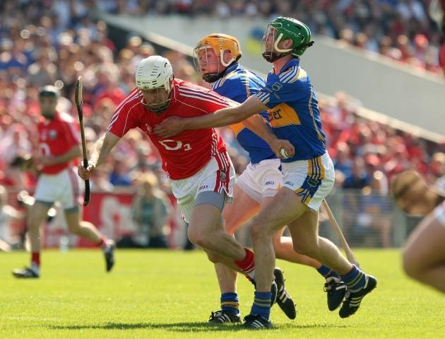 Seamus Callanan and Declan Fanning tackle Timmy McCarthy