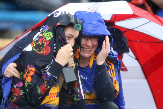 Supporters take shelter from a heavy shower