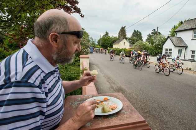 Billy Finnegan eats his dinner on his front wall as the riders of An Post Rás pass through Rathcormac