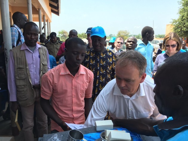 Minister of State for International Development and the Diaspora Joe McHugh giving an emergency supply package to a newly arrived South Sudanese refugee at the Nyumanzi Refugee Transit centre in northern Uganda