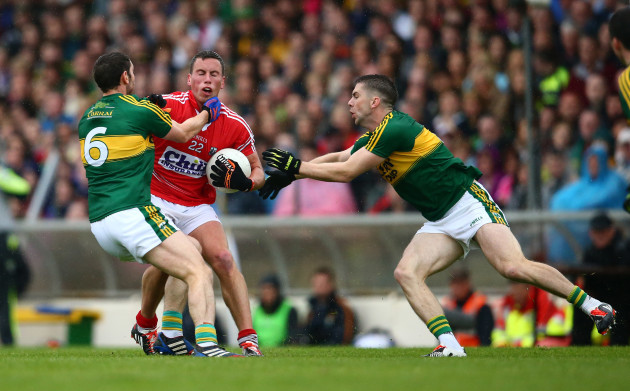 Killian Young and Marc O'Se tackle Patrick Kelly