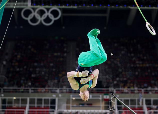 Kieran Behan dismounts from the rings
