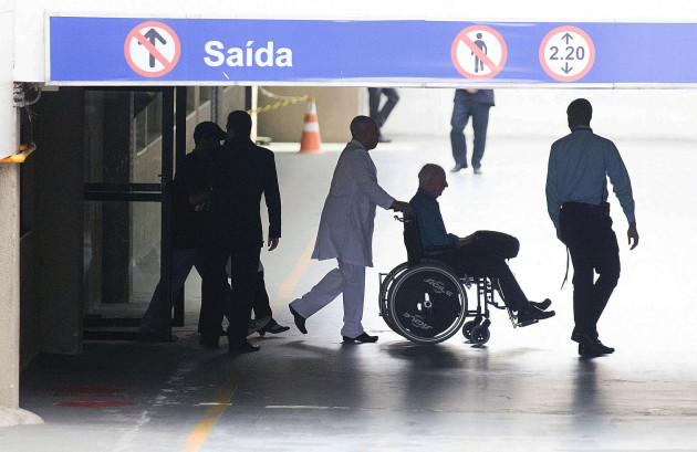 Pat Hickey is escorted from hospital