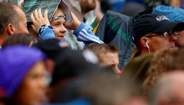 A Dublin fan shelters from the rain