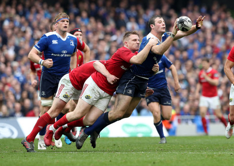 Leinster's Robbie Henshaw is tackled by Munster's Rory Scannell