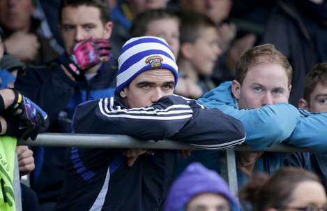 Ger Brennan watches from the stands after being sent off early in the game