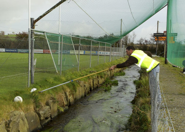 A steward at Clonakilty GAA attempts to retrieve the ball over a stream during the teams warm up
