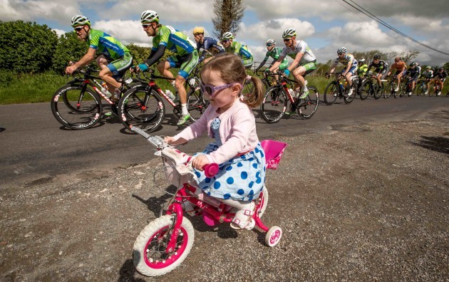 3 year old Anna Crombie rides her bike as the An Post Rás passes through Rahugh