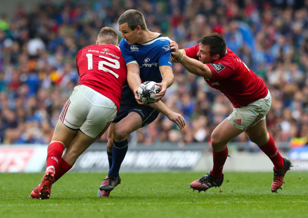 Leinster's Jonathan Sexton is tackled by Munster's Rory Scannell and Niall Scannell